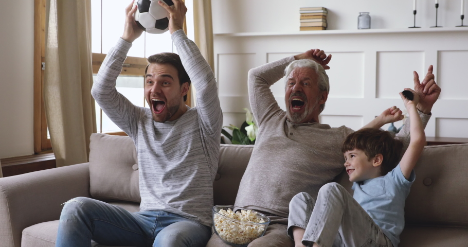 Excited three generation men family grandson young father and old grandfather fans hold soccer ball remote control watch tv sport game celebrate goal television team victory in tv match sit on sofa #1044003436