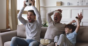 Excited three generation men family grandson young father and old grandfather fans hold soccer ball remote control watch tv sport game celebrate goal television team victory in tv match sit on sofa