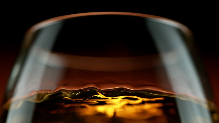 Super slow motion of waving whiskey, cognac or rum in macro shot. Filmed on high speed cinema camera, 1000 fps | Shutterstock HD Video #1044009553