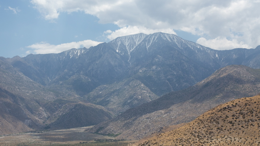 Time lapse wide shot of approaching clouds in blue sky casting shadows on a snow covered Mount San Jacinto and desert foothills in the San Bernardino Mountains by Palm Springs California on a hazy day
