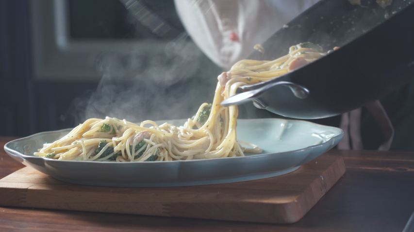 Chef puts finished spaghetti pasta from pan onto a plate in a restaurant kitchen. Food ingredient. Cooking on cuisine. Cooked for gourmet. Prepare food to eat. Gastronomy culinary. Delicious dinner.   Shutterstock HD Video #1044034663