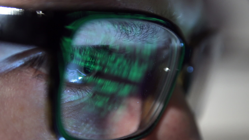 detail of a person's eye looks, a hacker code is reflected on glasses Royalty-Free Stock Footage #1044042871