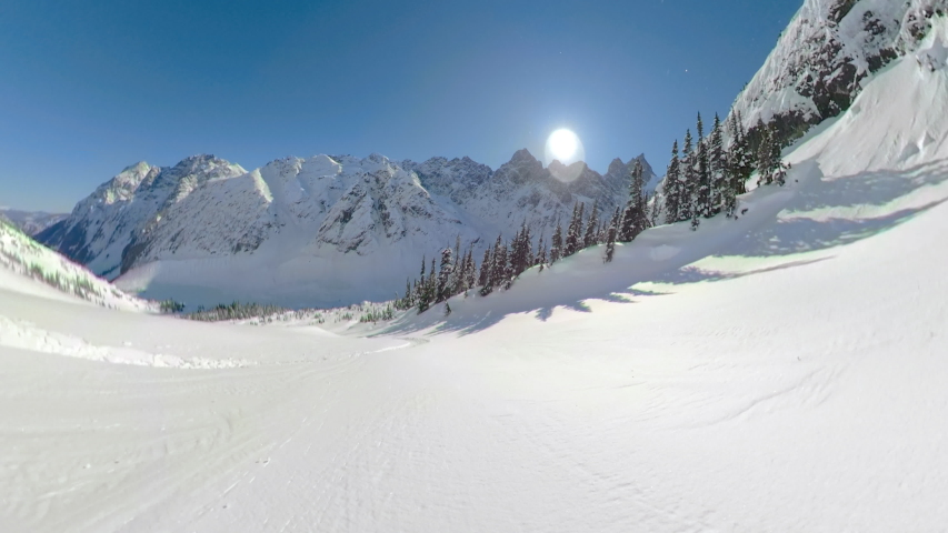 POV: Awesome first person shot of snowboarding off piste in the gorgeous Canadian mountains. Shredding the fresh powder snow during a heliboarding trip in British Columbia. Beautiful wintry landscape.