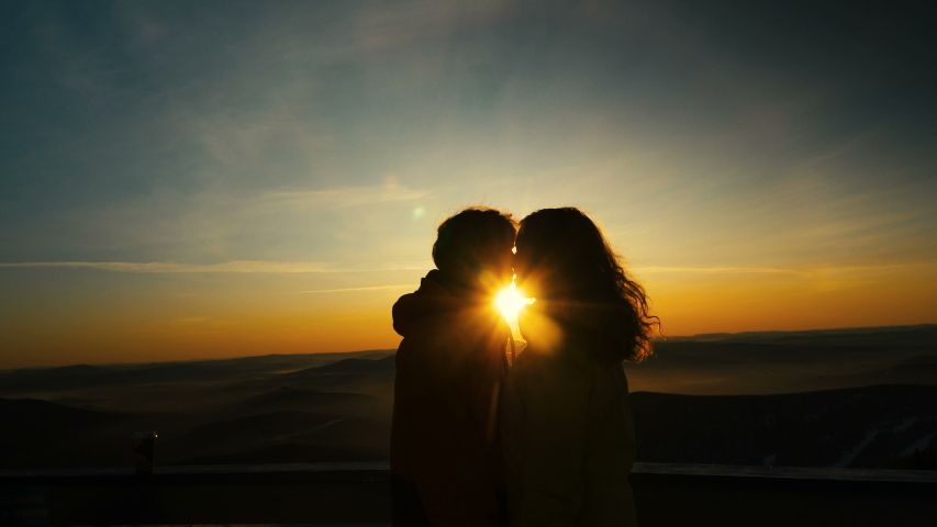 Couple in love kisses standing on snowy slope at back pictorial orange sunset between heads against hilly landscape in mist
