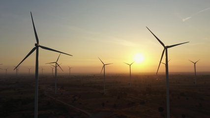 Aerial view of Wind turbines of save Energy save world in video 4k format. aerial shot on sunset. drone footage wind turbines at sunrise with beautiful clouds. Global warming concept and green energy.