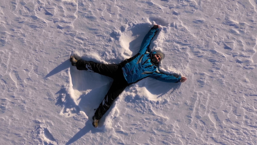 Top aerial view of happy smiling middle aged man making snow angel. Winter outdoor activity and happy lifestyle concept.