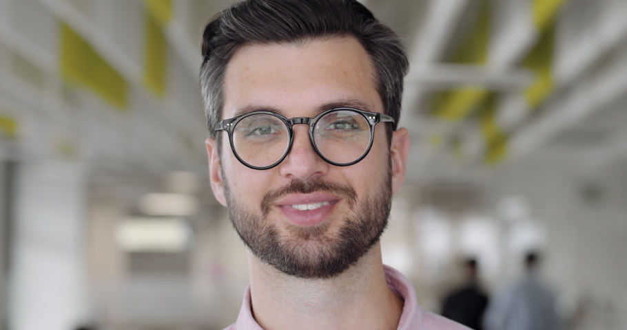 Close up of happy handsome man in glassess looking to camera and smiling. Bearded male office worker in good mood. People portraits. Concept of emotions. Blurred office background | Shutterstock HD Video #1044054967