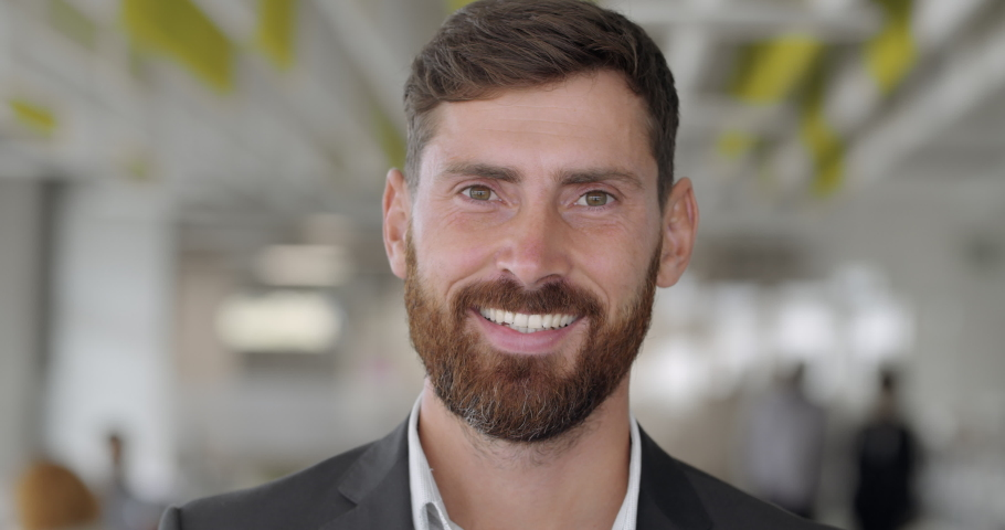 Close up of cheerful male boss with beard looking to camera and smiling. Good looking caucasian man team leader in modern company office. Portraits. Concept of people and emotions | Shutterstock HD Video #1044054973