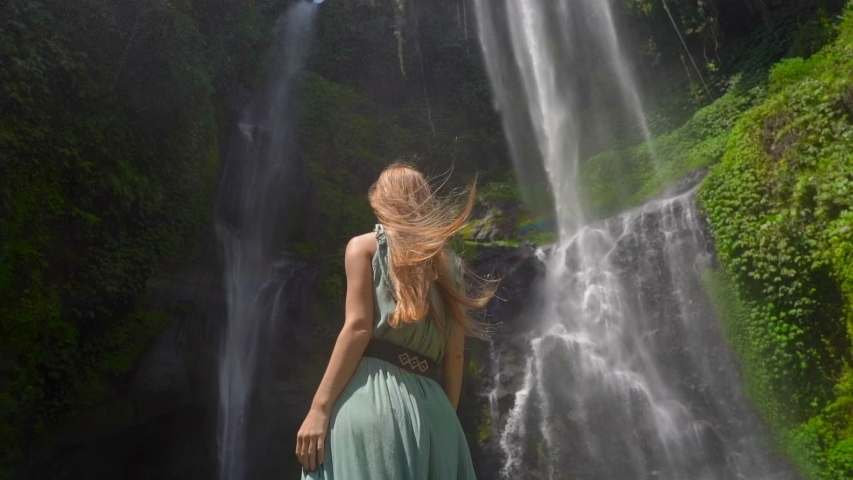 Young woman tourist visits the biggest waterfall on the Bali island - the Sekumpul waterfall. Slowmotion shot. Travel to Bali concept Royalty-Free Stock Footage #1044058759