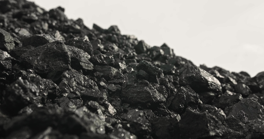 Coal close-up. Panorama of pile of coal in slow motion. Carbon concept in 4k. Shiny pile of anthracite on white background. Stone ore close-up in slow motion. Natural minerals
