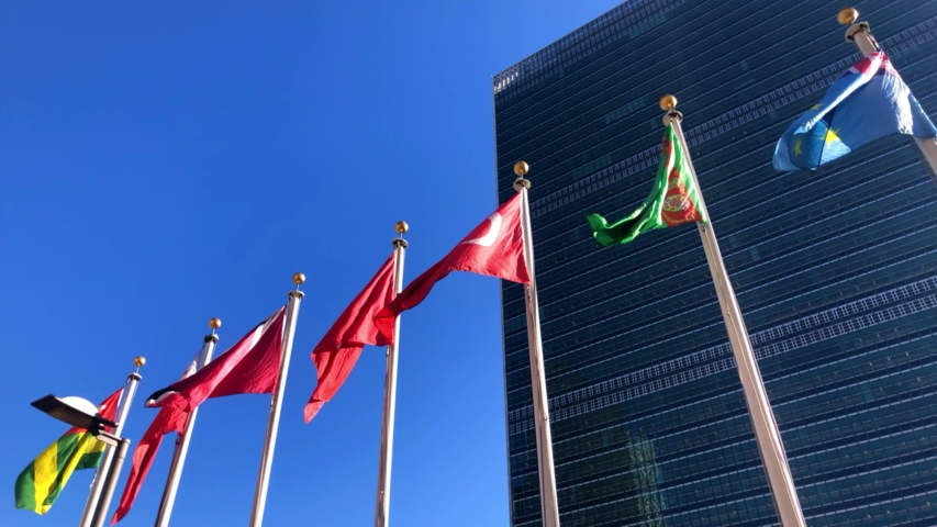 New York - January 2, 2020: The United Nations building in Manhattan, the official headquarters of the UN since 1952, and the flags of its member countries.