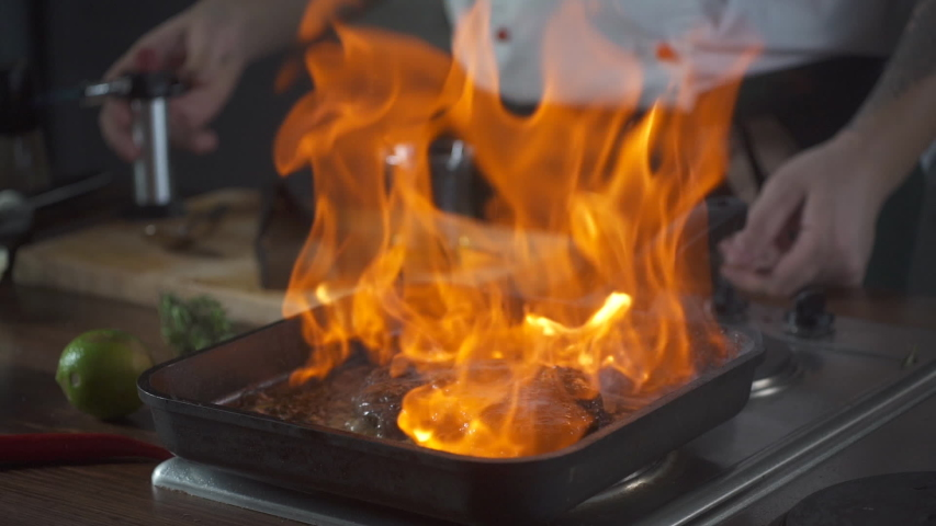 Chef making steak fillet mignon in flambe style on a grill pan. Oil and alcohol fire with open flames. Food on cuisine. Nutrition in gourmet kitchen. Making meal. Prepare food to eat. Delicious dish.