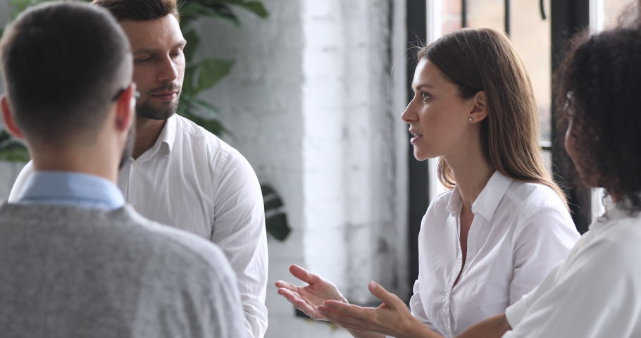 Confident young female mentor corporate leader manager counselor communicate with multiracial business professional team people teaching interns staff group engaged in discussion at training meeting Royalty-Free Stock Footage #1044100438