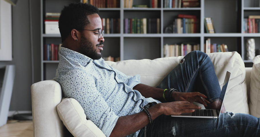 Relaxed serious millennial african ethnic guy student freelancer using laptop device leaning on sofa at home office, focused mixed race entrepreneur working distantly typing on notebook in apartment