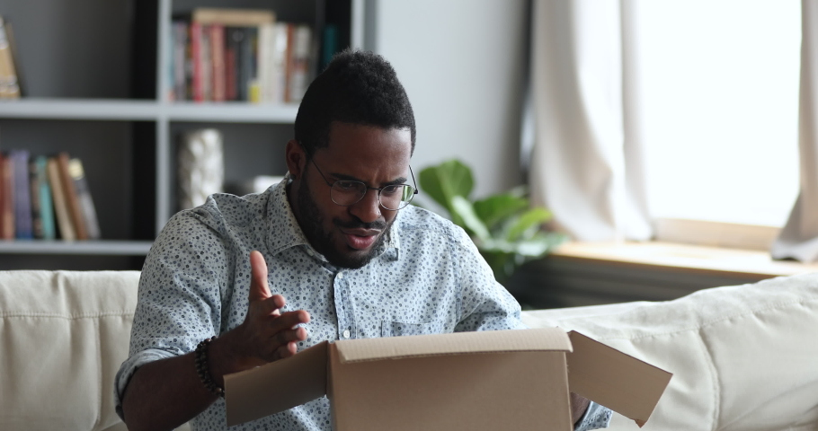 Frustrated dissatisfied african man customer open cardboard box receive damaged wrong parcel, disappointed male consumer having problem with bad fake online shop post shipping delivery order concept   Shutterstock HD Video #1044100471