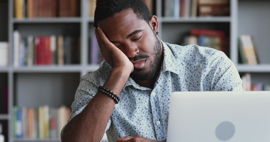 Funny bored at work african american businessman worker falling asleep at office desk, sleepy deprived tired mixed race male student employee sleeping at workplace near laptop feel overworked concept | Shutterstock HD Video #1044100486