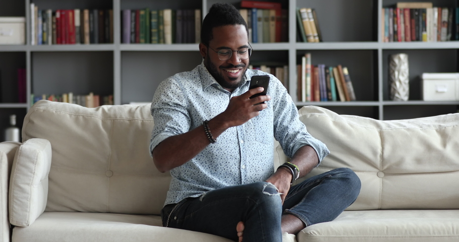 Tech addict millennial african man sitting on couch using smart phone, smiling young adult mixed race male user hipster texting sms in social media dating apps enjoy easy online communication at home Royalty-Free Stock Footage #1044100489