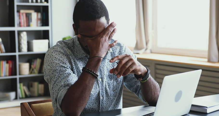 Tired young african mixed race businessman professional student take off eyeglasses massaging dry itchy irritated eyes feel eye strain concept headache fatigue after office computer work sit at desk | Shutterstock HD Video #1044100510