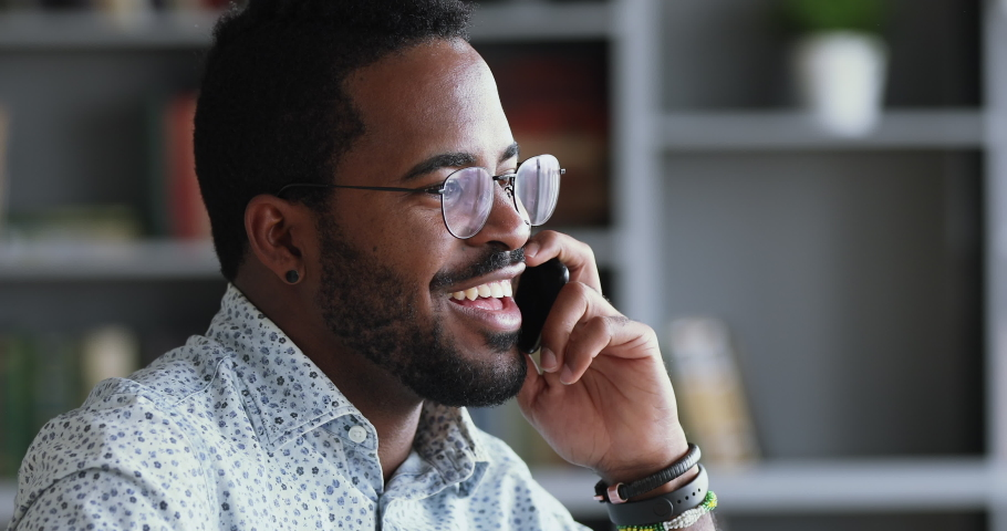 Smiling young adult mixed race professional casual businessman making business call talking on the phone in office, happy afro american salesman enjoying mobile conversation indoors, close up view