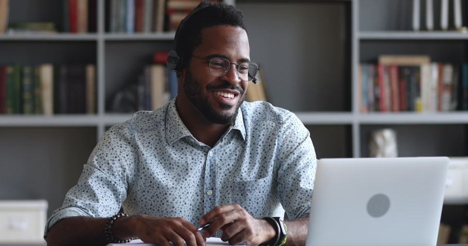 Smiling african male student wear headset elearning study with online tutor teacher talk conference calling do video chat learn language make notes sit at home office desk look at laptop computer | Shutterstock HD Video #1044100525
