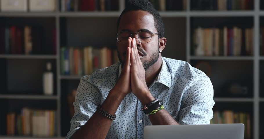 Serious african man asking for help concerned about problem or concentrating mind at work, religious mixed race male student worker sit with eyes closed put hands in prayer praying with hope concept