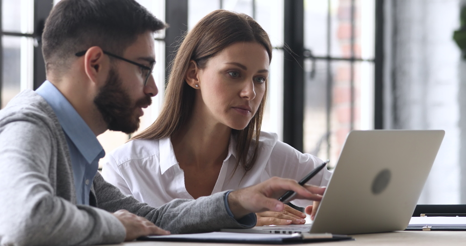 Male professional mentor helping female client teach intern training new worker consult customer explain online business services computer corporate software look at laptop screen at office meeting