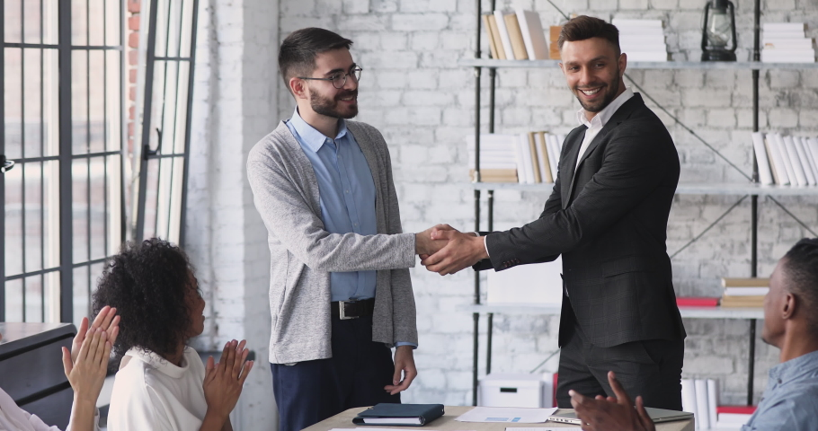 Happy company manager handshake promote praise male intern worker in office, motivated young employee rewarded appreciated for good work results get positive feedback concept team applause at meeting