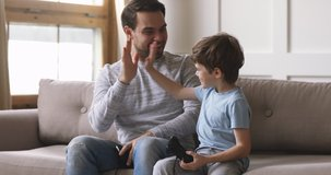 Overjoyed young adult dad and cute child son gamers winners playing winning video game, excited father having fun with kid boy give high five holding celebrating videogame victory at home