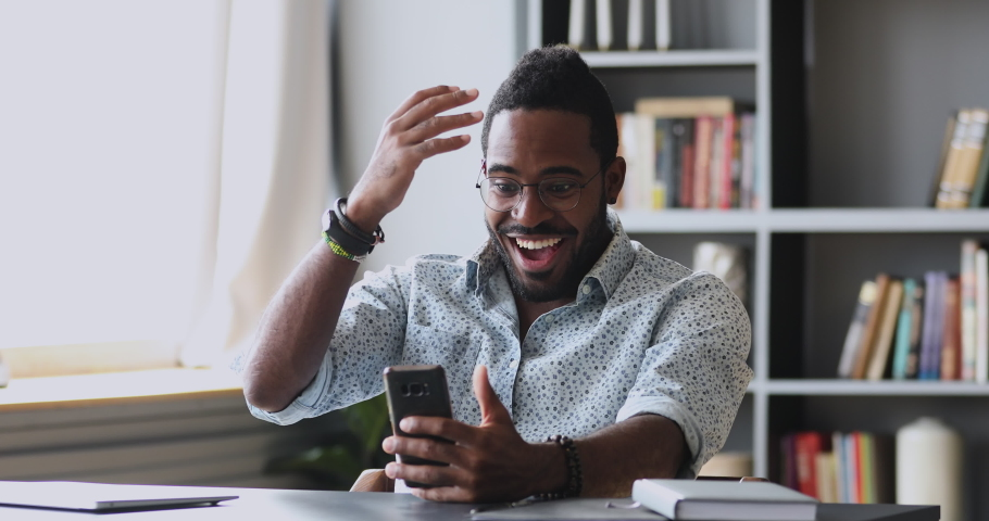 Excited african guy student winner hold smartphone feel amazed overjoyed with mobile online bet bid app game win, happy ecstatic mixed race male user use look at cell phone celebrate read good news