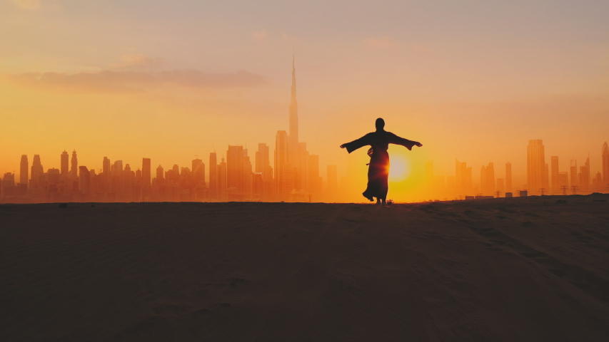 Arabic woman weared in traditional UAE dress - abayain rising her hands on the sunset at a desert with Dubai city silhouette on the background. Royalty-Free Stock Footage #1044117208