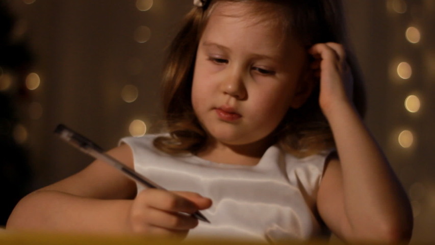 Child is writing a letter in room, at night amid the lights, preparing for holiday. Holidays and celebrations concept. Portrait caucasian baby girl close up.