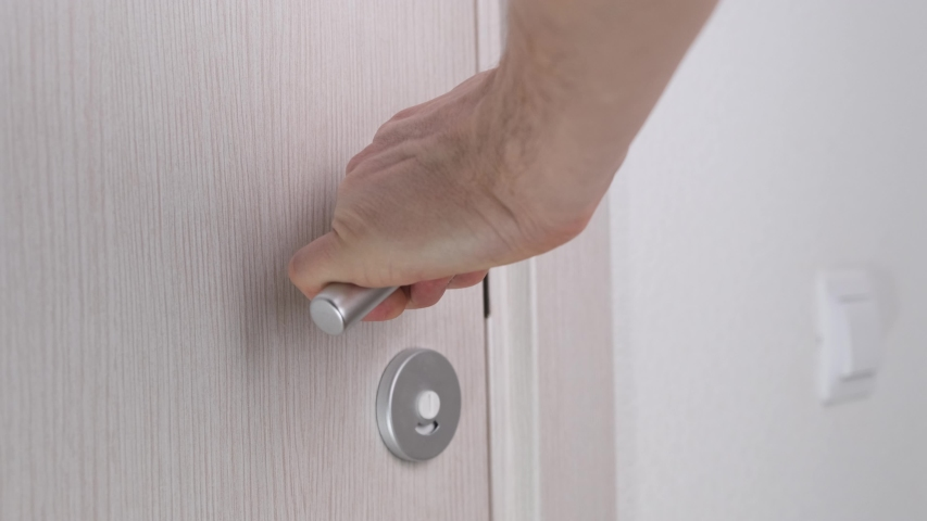 Men's hand opens wooden door in white room. Close up. Royalty-Free Stock Footage #1044124942