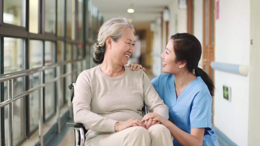 friendly asian nursing home employee talking to senior woman resident happy and smiling Royalty-Free Stock Footage #1044134668