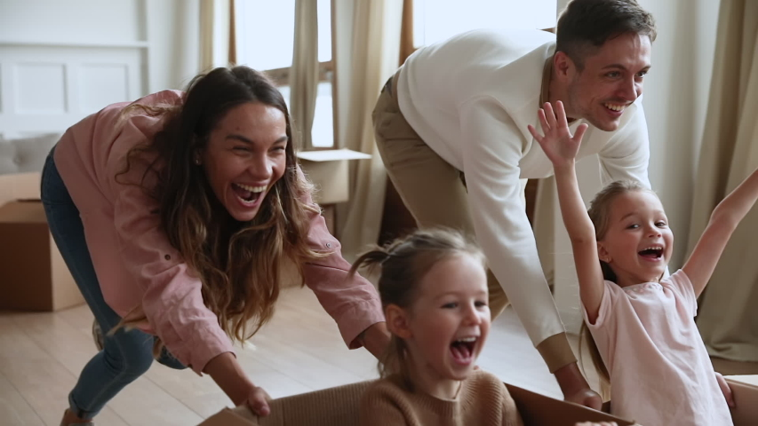Excited happy young parents run push cardboard boxes with little cute children daughters ride inside, family homeowners playing having fun on moving day celebrate mortgage relocation removals concept