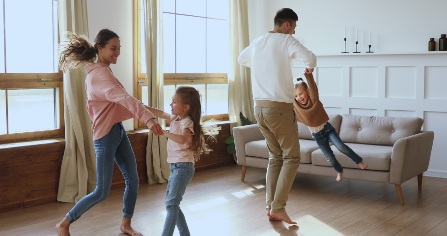 Happy active family young adult parents mum dad and cute little children daughters holding hands dancing jumping together in living room interior enjoying funny weekend activity in modern apartment