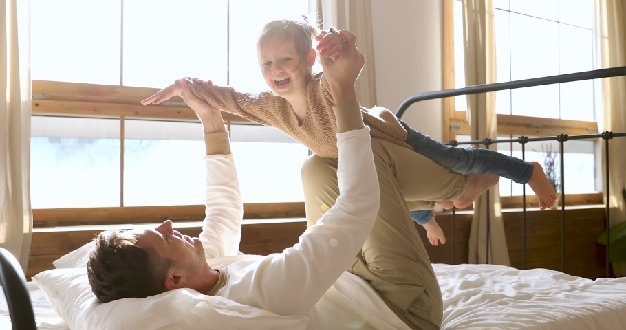 Happy family young dad lifting cute little kid daughter up fly as airplane having fun enjoying weekend sunny morning in bed, carefree adorable small child playing with parent father in modern bedroom #1044147376