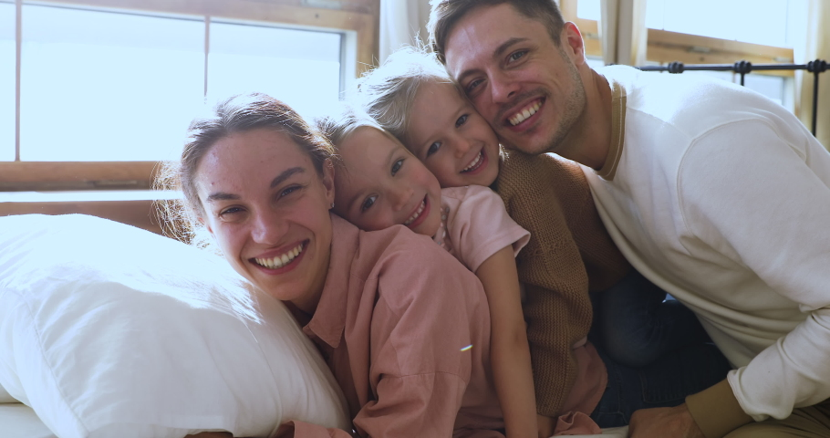 Happy funny beautiful family of four bonding laughing relaxing on comfortable bed looking at camera, cheerful young parents with cute little kids daughters lay in bedroom in morning, closeup portrait Royalty-Free Stock Footage #1044147385