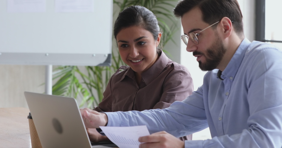 Diverse indian and caucasian colleagues discuss financial data analyzing marketing result in report using laptop having business conversation help coworker with corporate project sit at office desk Royalty-Free Stock Footage #1044147433