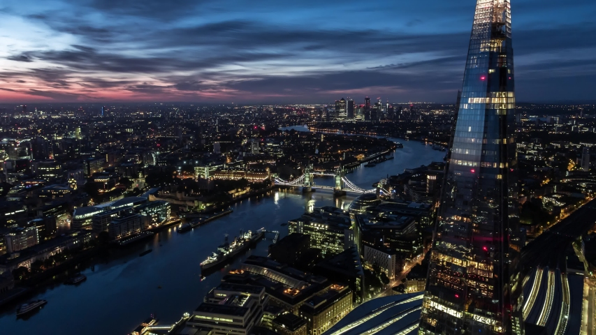 Establishing Aerial View Shot of London City Skyline Shard and Tower Bridge in foreground, Canary Wharf in background United Kingdom sunrise dusk wonderful colors of the sky