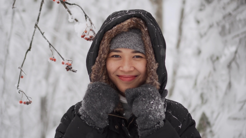 Portrait of cute girl in snowy park, she is warming herself with hood and winter jacket among trees covered with snow. Pretty smiling asian model outdoor in winter | Shutterstock HD Video #1044162814