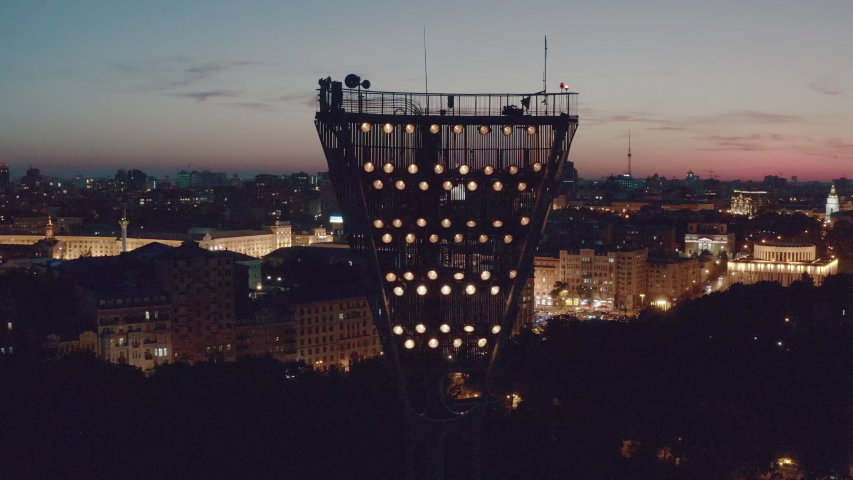 Switching on the light tower of a football stadium against a sunset and a night city cinematic smooth movement of a drone