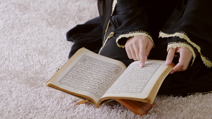 Asian muslim young woman sitting reads a koran book indoors at home, Study education of religious teachings | Shutterstock HD Video #1044174868