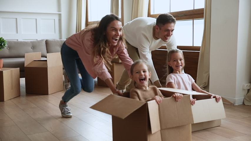Funny active family playing on moving day, excited happy adult parents mom dad pushing cardboard boxes with cute little kids sit inside having fun packing relocate into new home concept, slow motion #1044184111