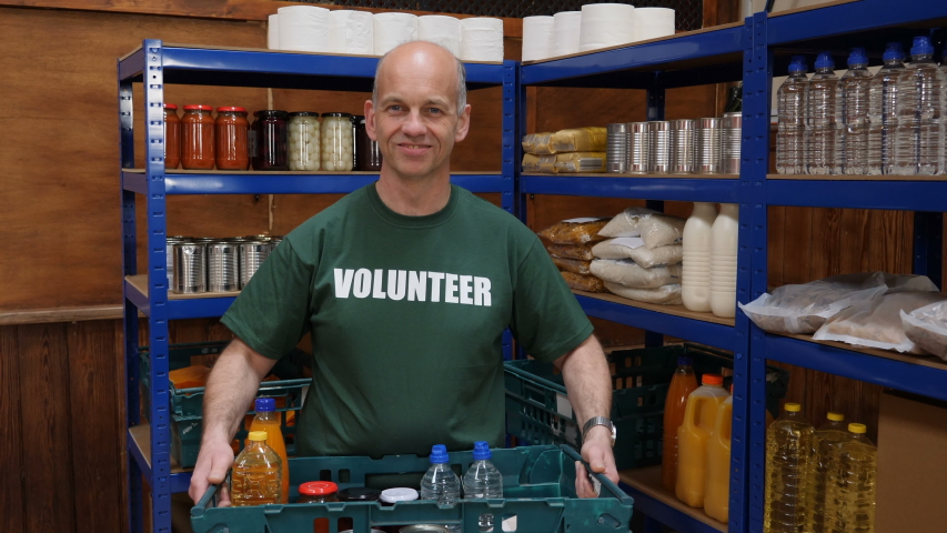 Food Bank male volunteer portrait - The man is holding a crate of food to help people in poverty and with social issues. Slow motion. | Shutterstock HD Video #1044191047