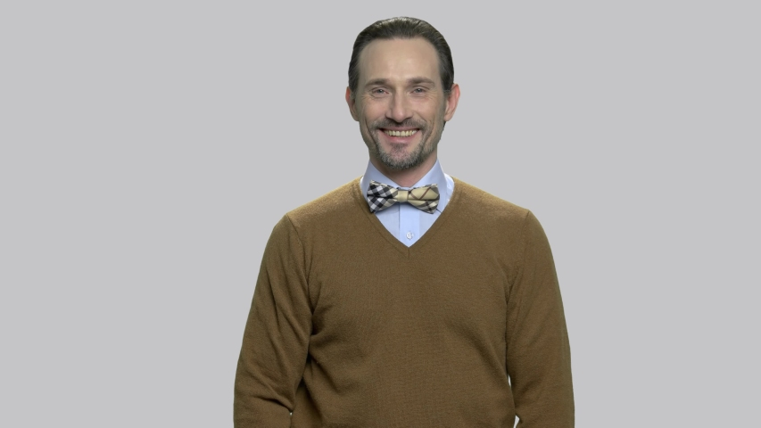 Handsome bearded man with thumb up gesture. Smiling caucasian man with bow-tie giving thumb up sign against gray background. Everything is ok concept.