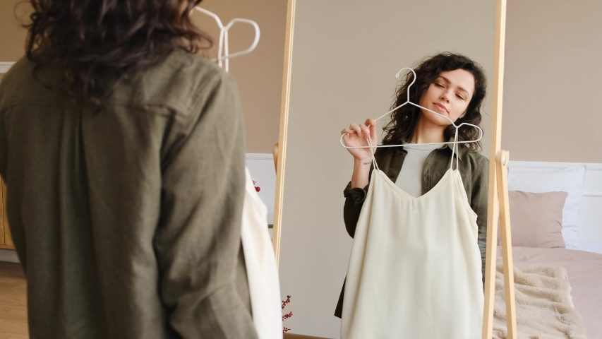 A young woman is going to a meeting, chooses clothes in front of a mirror. Hard choice routine of what clothes to wear.  | Shutterstock HD Video #1044201190