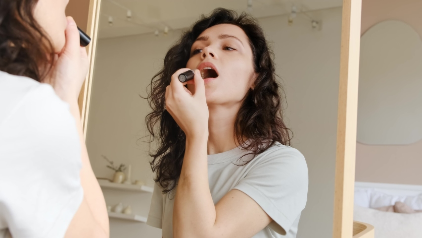 Young female holding lipstick in her hands and paints lips prepare getting ready in the morning. She looks at herself in the mirror and smiles. Woman doing makeup. Get ready for a date. | Shutterstock HD Video #1044204808