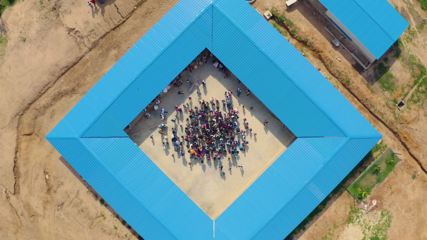 Aerial View Zoom Out of School with Kids in African Savannah, Angola, Day Light