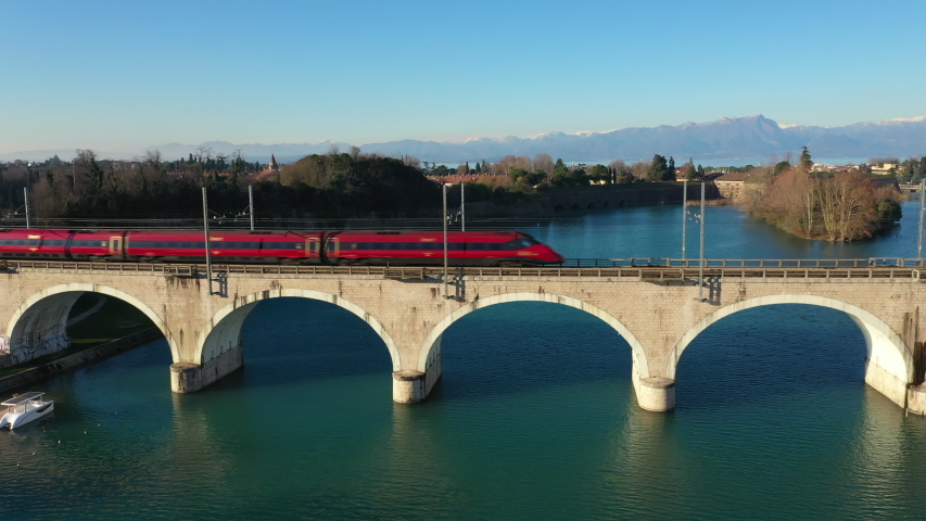 High-speed train moving on an arch bridge over the Mincio River in the city of Peschiera del Garda, Italy. In the background the Alps in the snow. The clear blue sky. Bridge reflection in water