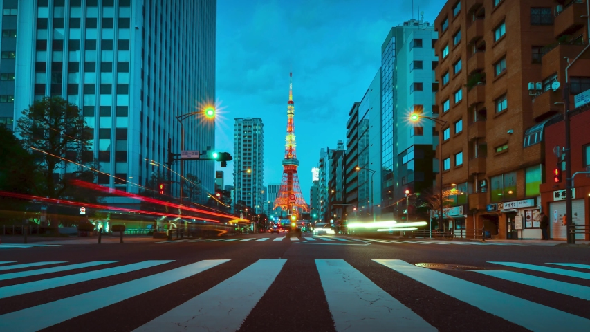 Time-lapse illumination view of business area street with view of Tokyo Tower in sunset night time. Night time Tokyo famous tourist attraction.Tokyo Olympic 2020 4K UHD video of Tokyo city in japan